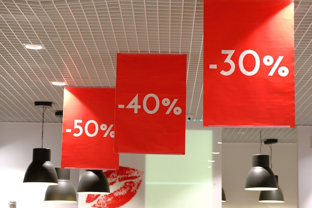 Flags with signs advertising sale 30%, 40%, 50% at shopping mall.