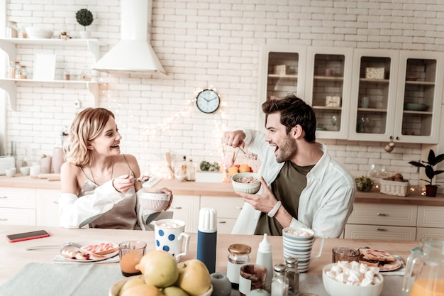 Flakes. bearded handsome positive man in a white shirt looking cheerful while eating flakes for breakfast