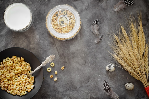 Flakes for breakfast and a glass of milk on a table with wheat and quail eggs.