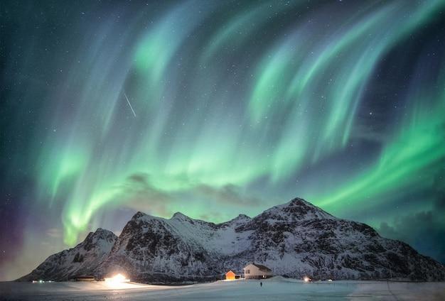 Flakstadのイルミネーションハウスが付いている雪の山脈の上の星空とオーロラ