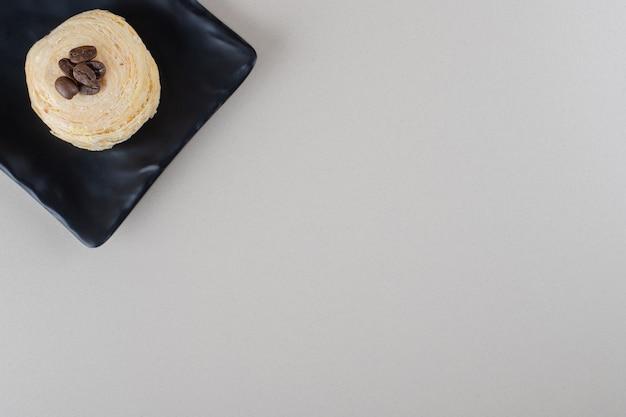 大理石の背景の大皿にコーヒー豆をトッピングしたフレーク状のケーキ。