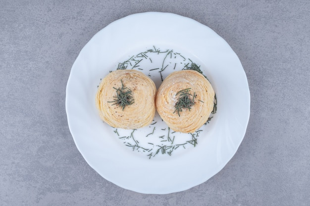 大理石のテーブルの松の葉で飾られた大皿にフレーク状のケーキ。