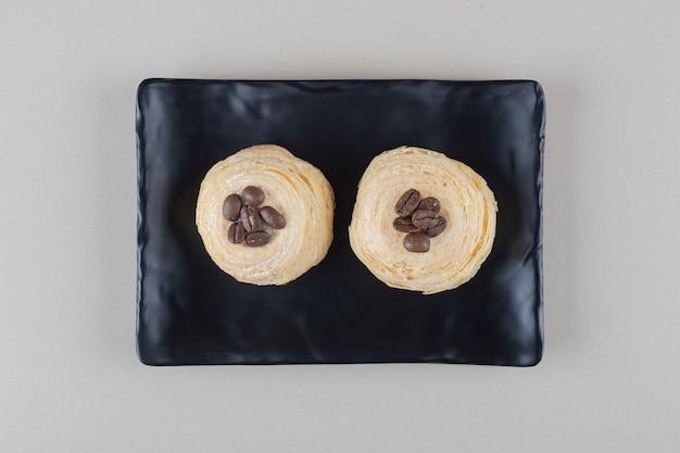 大理石の背景の大皿にコーヒー豆のトッピングとフレーク状のケーキ。