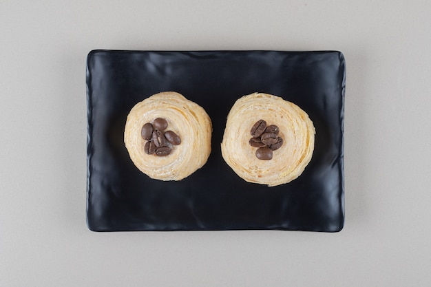 Torte a fiocchi con condimenti di chicchi di caffè su un piatto su sfondo di marmo.