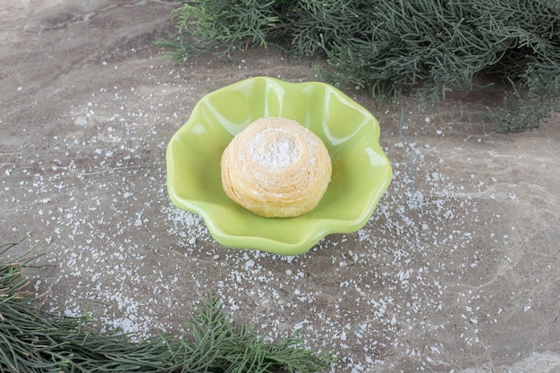 大理石の表面の松の枝の間の小さなボウルにフレーク状のクッキー