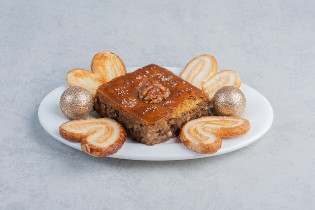 Слоеное печенье и пахлава на блюде с безделушкой на мраморной поверхности