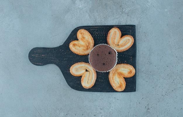 大理石の背景に黒板にフレーク状のクッキーとカップケーキ。高品質の写真