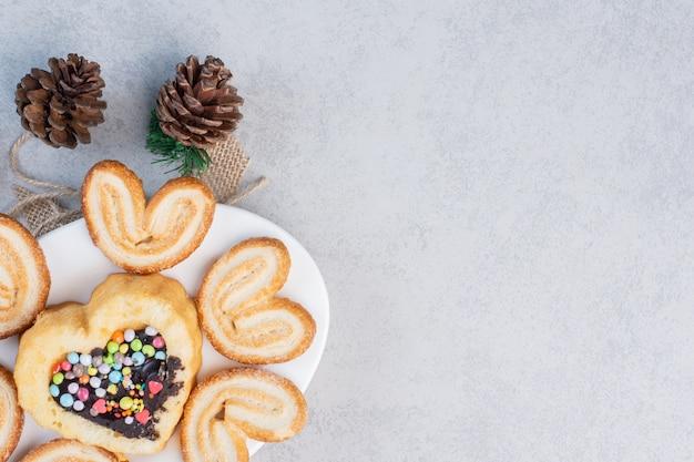 大理石のテーブルの松ぼっくりの横にある大皿にフレーク状のクッキーと小さなケーキ。 無料写真
