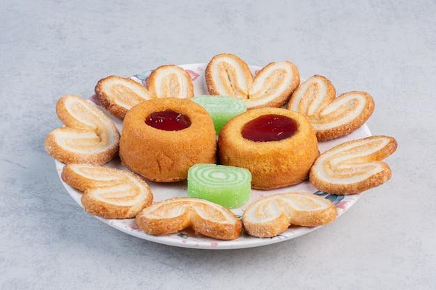 大理石のテーブルの大皿にフレーク状のクッキー、マーマレード、ゼリーを詰めたケーキ。