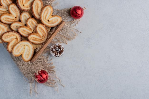 나무 바구니에 쌓여 있고 대리석 표면에 크리스마스 장식으로 둘러싸인 색다른 쿠키