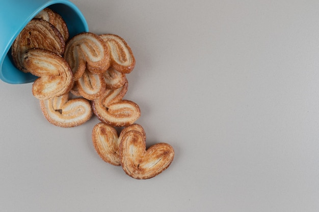Flaky cookies spilling out of a bowl on marble background.