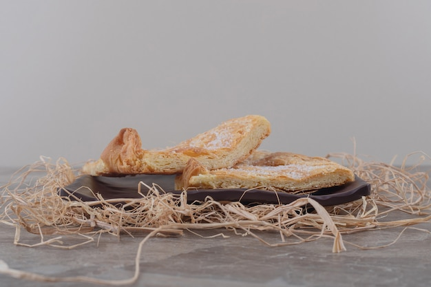 Flaky flatbread on platter on a pile of straw on marble