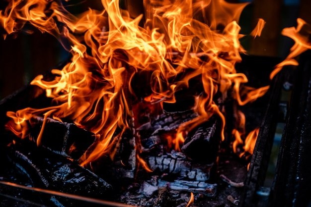 Flame of fire in a fire with burnt wood abstract fire flame background