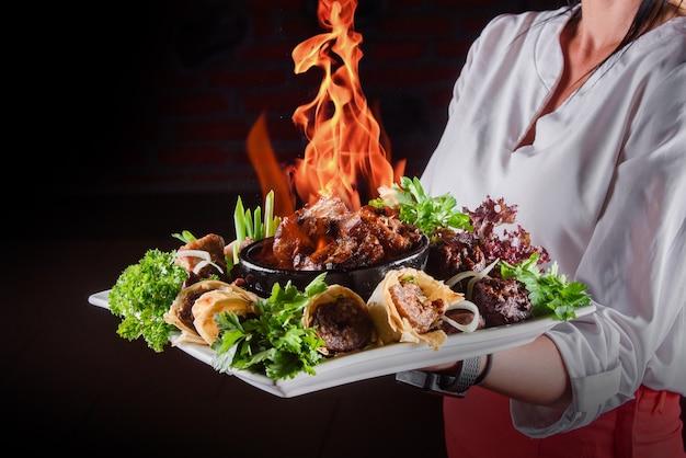 粘土のボウルに肉を燃やします。野菜のグリル、ハーブで飾られたピタパンのケバブを添えたプレートに火をつけた肉。