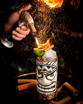 Flamed cocktail with ice and fruits