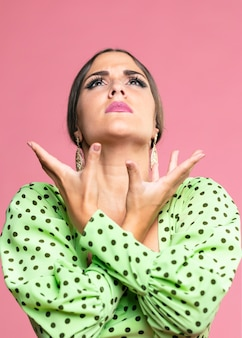 Flamenca dancer looking up with pink background