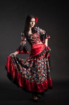 Танцовщица фламенко в национальном цыганском платье на темном фоне
