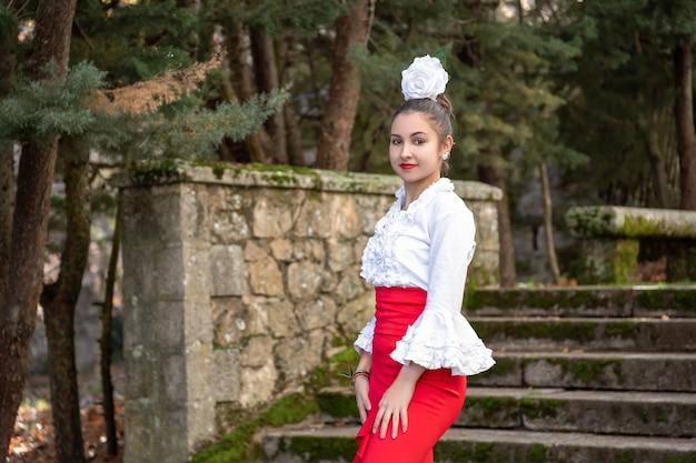 Танцовщица фламенко в красном платье с рубашкой и белым цветком на голове смотрит в камеру.