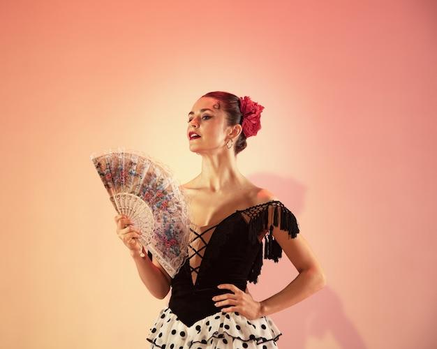 플라멩코 댄서. 빨간 장미와 스페인 손 부채가 스튜디오에서 포즈를 취하고 춤을 추는 스페인 여자 집시. 열정적인 스페인 기질과 춤에 대한 열정. 인간의 감정 개념