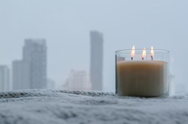 Пламя горит на расплывчатом аромате свечи в зимний период у окна. дзен и концепция релаксации.