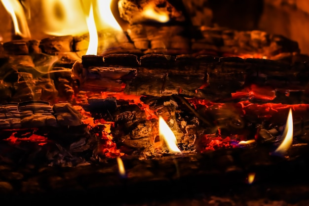 Пламя огня и раскаленные угли сгоревших дров в камине