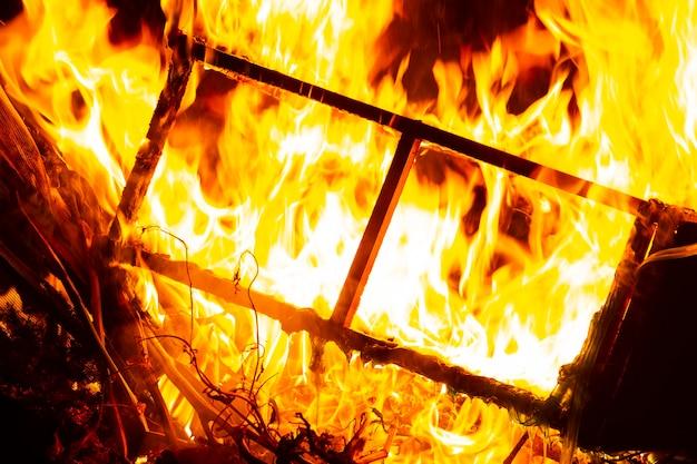 家の窓を破壊する火の炎、