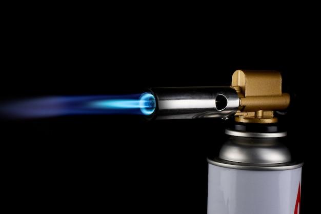 Огнемет горелки газовой паяльной лампы зажигание с синим пламенем огня на черном фоне