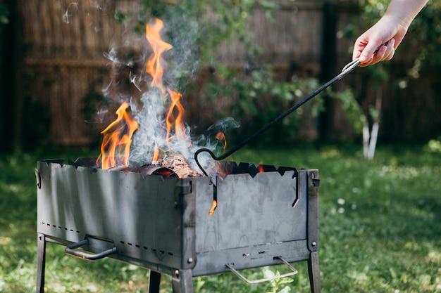 Flaming barbecue grill in the yard in summertime
