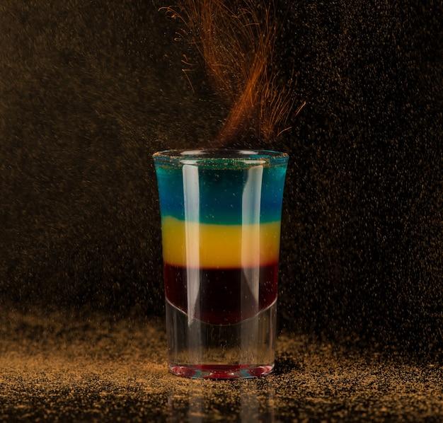 黒の背景、孤立したショットグラスにシナモンと燃えるようなカクテル