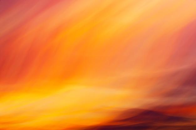 創造的な抽象的な背景としてカメラの動きで撮影された燃えるような神秘的な色の夕日の雲