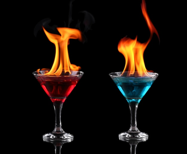 Flaming red and blue cocktails over black