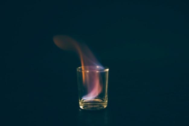 燃えるテキーラは、黒の背景にガラスを投げた