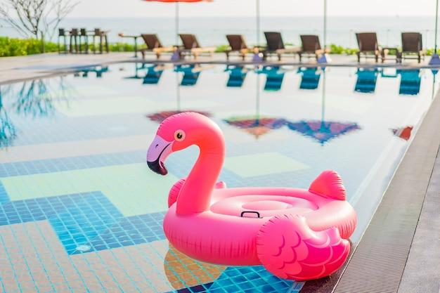 ホテルリゾートのスイミングプールの周りのフラミンゴフロート