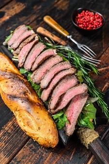 Сэндвич из багета flank steak с рукколой на разделочной доске