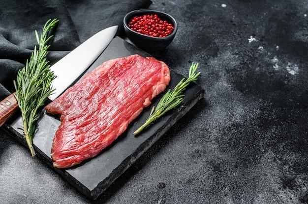 Фланк стейк. сырое мясо мраморной говядины блэк ангус. черный фон. вид сверху.