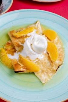 Flapjack with ice cream and orange