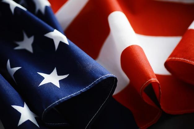 Размахивая флагом сша с волной. американский флаг на день памяти или 4 июля. крупный план американского флага на темном фоне