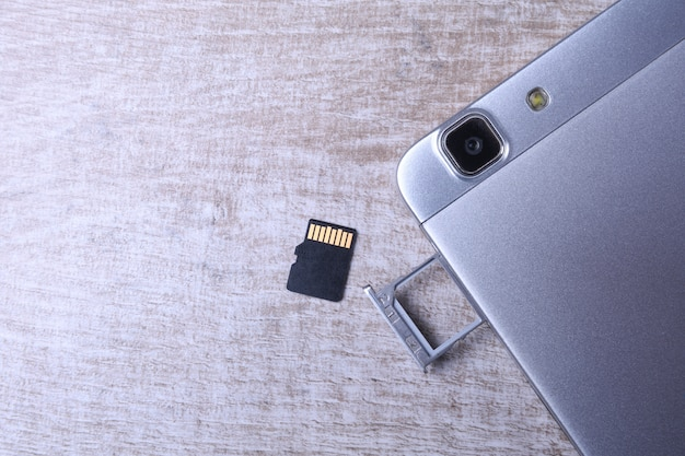 Flash memory data storage concept : a tray with a micro sd card. a memory card is used for storing digital information in portable electronic devices e.g mobile phone, tablets, etc