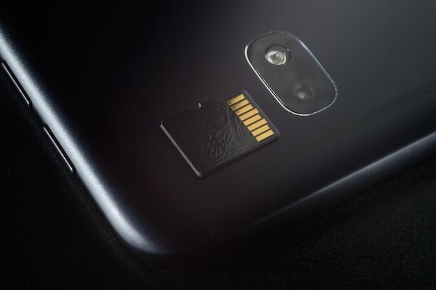 플래시 메모리 저장 개념 : 스마트 폰 배경에 마이크로 sd 카드. 메모리 카드는 휴대폰, 태블릿 등과 같은 휴대용 전자 장치에 디지털 정보를 저장하는 데 사용됩니다.