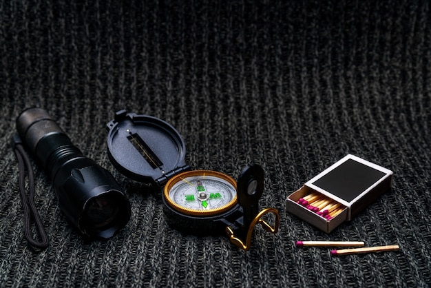 Flashlight, compass, matches on a gray fabric background