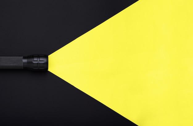 Фонарик включен с желтым лучом света на черном фоне