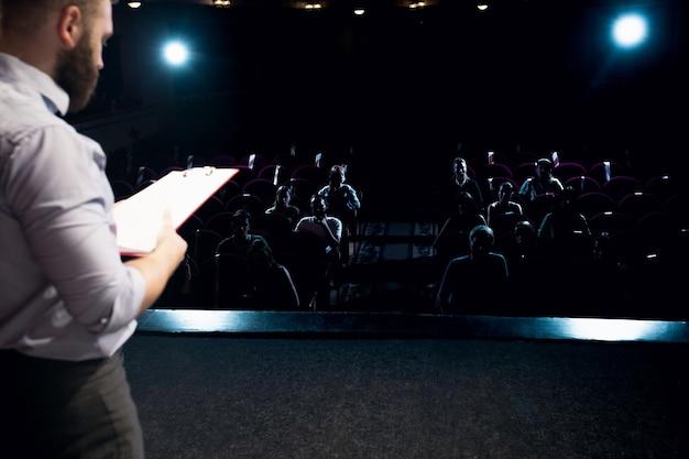 Фонари зала. спикер-мужчина дает представление в зале на семинаре. бизнес центр. вид сзади участников в аудитории. конференц-мероприятия, обучение. образование, встреча, бизнес-концепция.