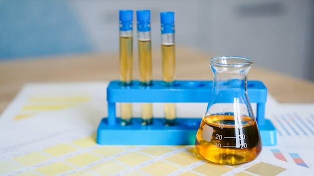 Колба и пробирки на стенде с мочой по медицинским цветовым схемам. понятие о лабораторных анализах, контроле рн.