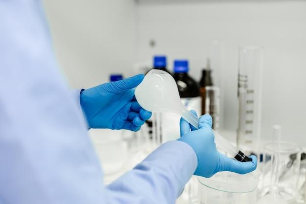 화학 액체를 테스트 튜브에 떨어 뜨리는 과학자 손에 플라스크
