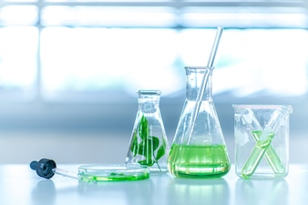 Flask of water green solution in science laboratory background