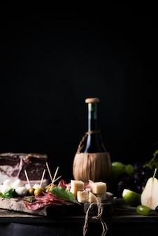 소박한 전통 이탈리아 음식이 있는 테이블에 있는 와인 플라스크. 신선한 팁칼 이탈리아 생활 방식