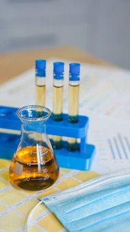 Flask and test tubes with urine on medical color schemes. the concept of laboratory analyzes, ph control. vertical photo