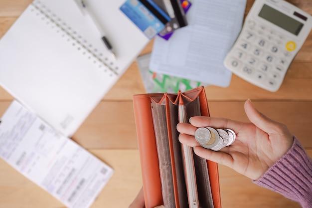 財布、電卓、ブックバンク、本、ペン、クレジットカードでコインを保持している手の女性を産む。