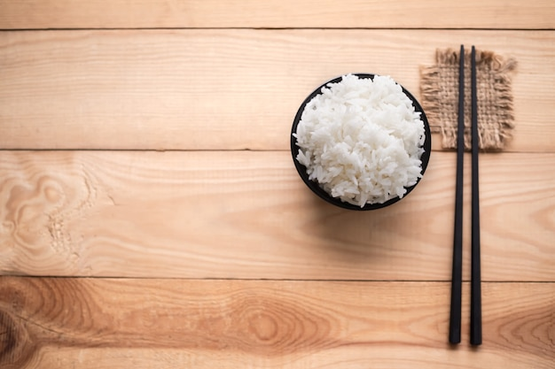 Flast lay white rice in black cup on wood background. thai staple food concept.