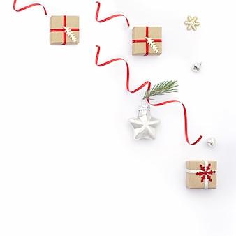 Плоская рождественская композиция с праздничными подарочными коробками, игрушкой звезды и еловыми ветками. концепция рождество, минимализм, праздник, продажа.